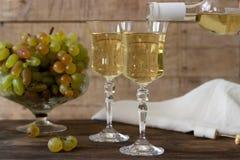 Vino blanco con los cubiletes y los manojos de cristal de la uva en un fondo de madera Imágenes de archivo libres de regalías