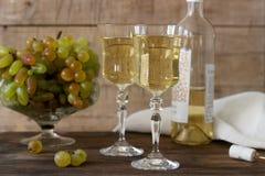Vino blanco con los cubiletes y los manojos de cristal de la uva en un fondo de madera Fotos de archivo libres de regalías