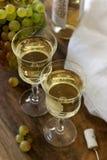 Vino blanco con los cubiletes y los manojos de cristal de la uva en un fondo de madera Imagenes de archivo