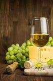 Vino blanco con queso y uvas Imagen de archivo