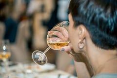 Vino blanco de consumición de la mujer en una recepción oficial en un restaurante Imagen de archivo
