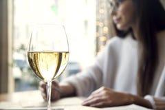 Vino blanco de la bebida de la mujer cerca de la ventana en restaurante Imágenes de archivo libres de regalías