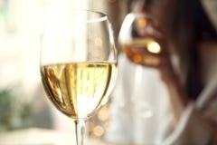 Vino blanco de la bebida de la mujer con el amigo en restaurante Imágenes de archivo libres de regalías