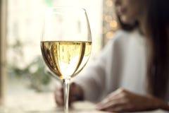 Vino blanco de la bebida de la mujer con el amigo en restaurante o un café Foto de archivo