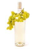 Vino blanco en botella y uvas Foto de archivo libre de regalías