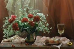 Vino blanco en un vidrio, melocotones y un ramo de rosas Imagenes de archivo