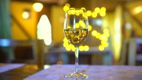 Vino blanco en vidrio en restaurante sobre fondo del centelleo de Bokeh del día de fiesta Imágenes de vídeo Vidrio de vino blanco almacen de video