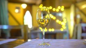 Vino blanco en vidrio en restaurante sobre fondo del centelleo de Bokeh del día de fiesta Imágenes de vídeo la mano del camarero  almacen de video