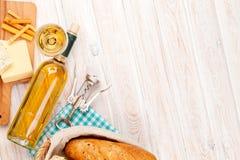 Vino blanco, queso y pan en el fondo de madera blanco de la tabla Imagen de archivo libre de regalías