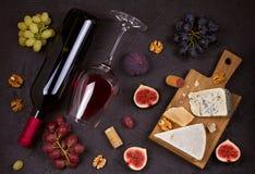 Vino blanco rojo y con la placa de queso Copas de vino con queso, uvas, higos y nueces en fondo negro Imagen de archivo libre de regalías