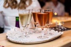 Vino blanco y color de rosa de la chispa en vidrios foto de archivo