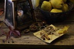 Vino blanco y peras en una cesta wattled y una linterna vieja Imagenes de archivo