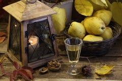 Vino blanco y peras en una cesta wattled y una linterna vieja Foto de archivo