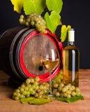 Vino blanco y uvas delante del barril viejo Imagen de archivo