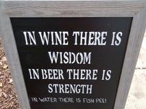 In vino c'è la saggezza in birra là è forza in acqua là è segno della pipi del pesce immagini stock