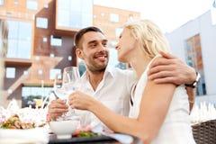 Vino de consumición de los pares felices en el restaurante al aire libre Imágenes de archivo libres de regalías