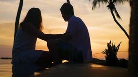 Vino de consumición del hombre y de la mujer en la puesta del sol de la playa Tarde romántica para dos