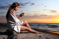 Vino de consumición hermoso de la mujer joven en la playa Foto de archivo libre de regalías