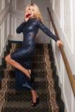 Vino de consumición rubio elegante en vestido de noche en las escaleras Fotos de archivo
