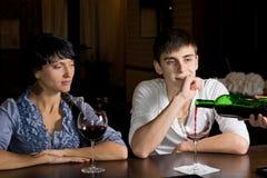 Vino di versamento del barista guardato da una giovane coppia immagini stock