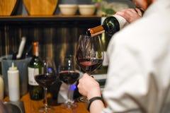 Vino di versamento del cameriere Sommelier abile che versa vino rosso nel vetro Bottiglia e bicchiere di vino della tenuta della  Fotografia Stock Libera da Diritti