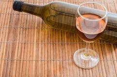 Vino di vetro con la bottiglia su superficie di legno Fotografie Stock
