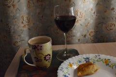 Vino domestico nel vetro con una torta mangiata per metà immagine stock libera da diritti