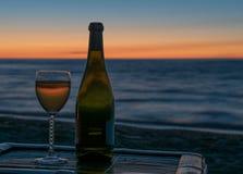 Vino en la playa en la puesta del sol Imágenes de archivo libres de regalías