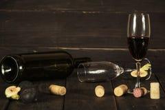Vino en un de cristal una botella vacía de higos en un fondo de madera oscuro Una copa de vino en una tabla de madera foto de archivo