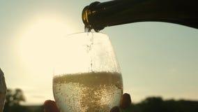 Vino espumoso Pour de la botella en las copas de vino transparentes contra una puesta del sol Trabajo en equipo de pares de amor  metrajes