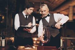 Vino experimentado del gusto de dos sommeliers El Sommelier vierte el vino rojo de la botella en la jarra foto de archivo