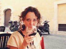 Vino hermoso de la prueba de la mujer mientras que se sienta en terraza en Roma Foto de archivo