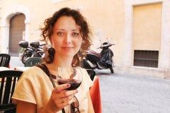 Vino hermoso de la prueba de la mujer mientras que se sienta en terraza en Roma Foto de archivo libre de regalías