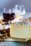 Vino licoroso dulce del postre en el vidrio, queso francés duro Tomme de Foto de archivo