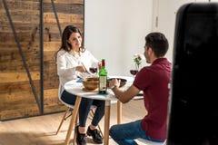Vino mangiante e bevente delle giovani coppie felici a casa fotografia stock libera da diritti