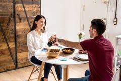 Vino mangiante e bevente delle giovani coppie felici a casa immagine stock