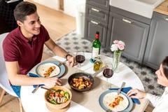 Vino mangiante e bevente delle giovani coppie felici a casa fotografie stock libere da diritti