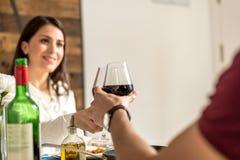Vino mangiante e bevente delle giovani coppie felici a casa fotografie stock