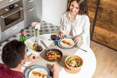 Vino mangiante e bevente delle giovani coppie felici a casa fotografia stock