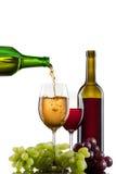 Vino que vierte en el vidrio con la uva y las botellas Imágenes de archivo libres de regalías