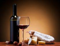 Vino, queso duro y salami Imagen de archivo libre de regalías