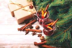 Vino reflexionado sobre caliente Ramas, regalos y conos de árbol de navidad Imagenes de archivo