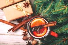 Vino reflexionado sobre caliente Ramas, regalos y conos de árbol de navidad Imagen de archivo