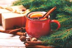Vino reflexionado sobre caliente Ramas, regalos y conos de árbol de navidad Fotografía de archivo