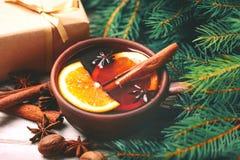 Vino reflexionado sobre caliente Ramas, regalos y conos de árbol de navidad Foto de archivo libre de regalías