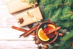 Vino reflexionado sobre caliente Ramas, regalos y conos de árbol de navidad Fotografía de archivo libre de regalías