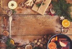 Vino reflexionado sobre en cazo con las especias y los ingredientes en b de madera Foto de archivo