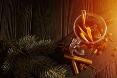 Vino reflexionado sobre en la tabla, los palillos de canela y la naranja de madera negros, visión superior imágenes de archivo libres de regalías