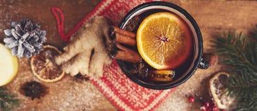 Vino reflexionado sobre en taza rústica con las especias y los ingredientes en de madera Foto de archivo
