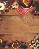 Vino reflexionado sobre en taza rústica con las especias y los ingredientes en de madera Imagen de archivo
